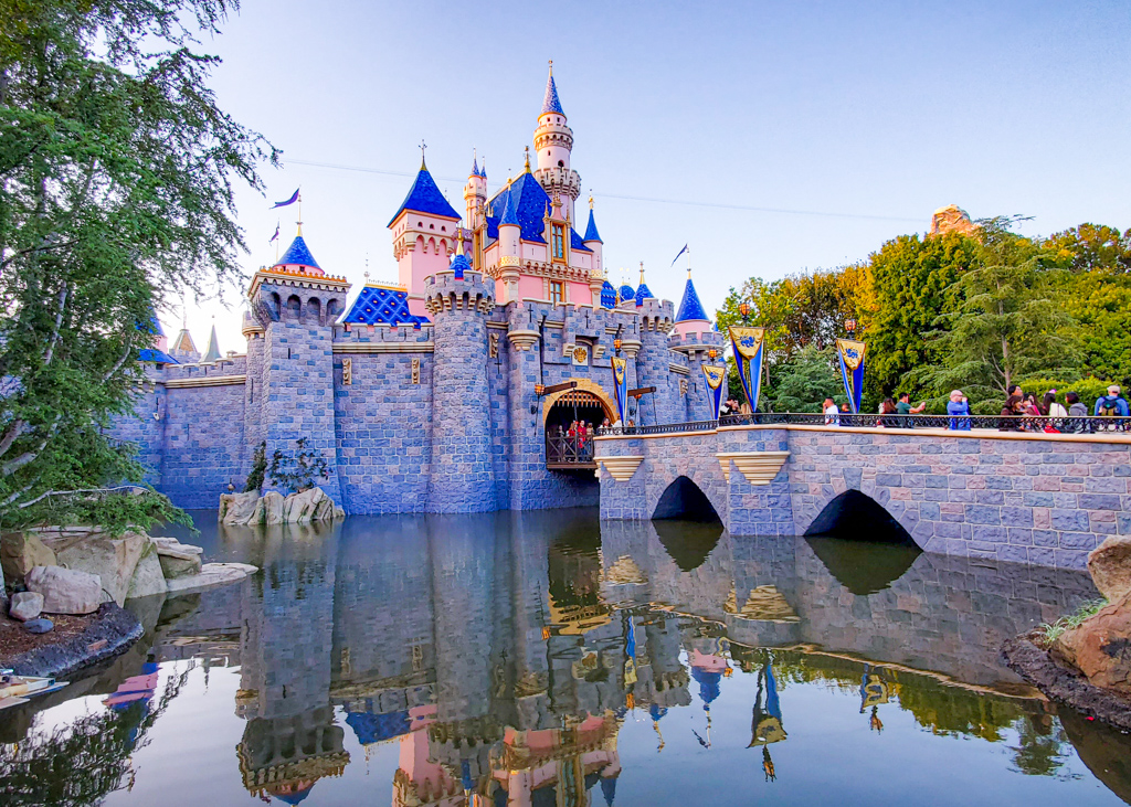 Disneyland Castle sideview showing the reflection of the castle in the water surrounding.