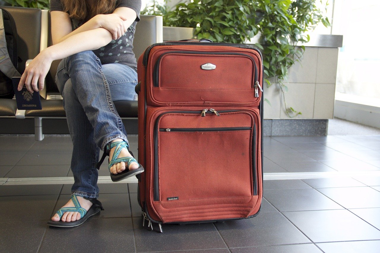 woman in airport with suitcase and passport
