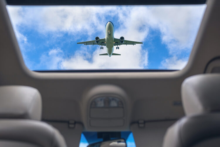 plane flying over car