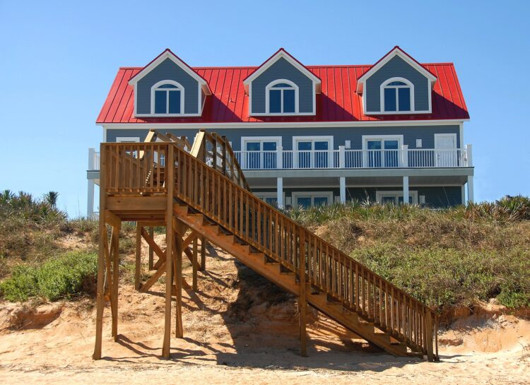beach front home with wood steps leading down to beach
