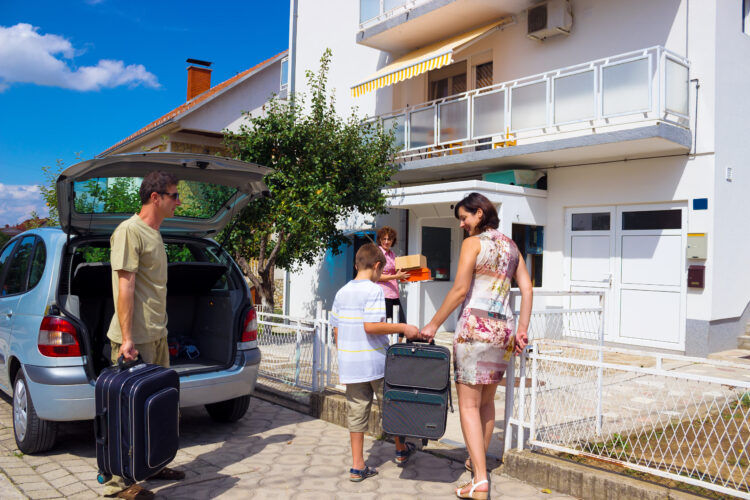 family unloading car in front of vacation home