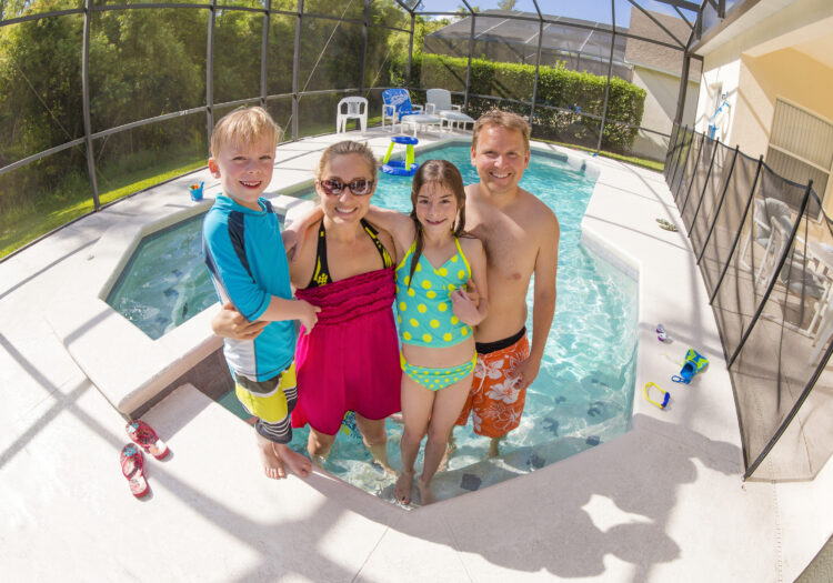 family standing in backyard of rental home by pool