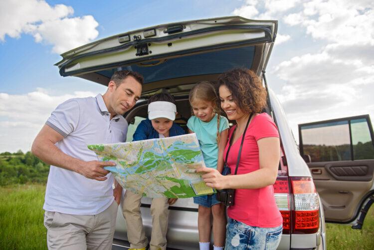 family at back of car looking at map