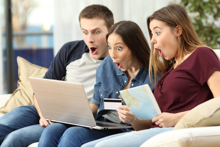 3 adults shocked faces looking at computer while one holds map