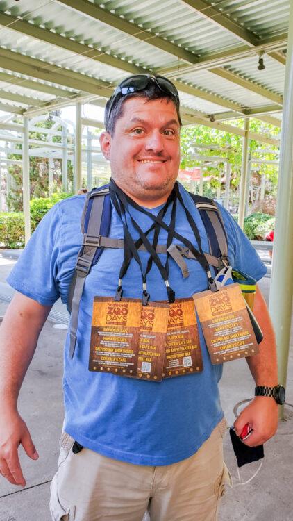 guy wearing multiple seaworld zoo days dining cards around neck