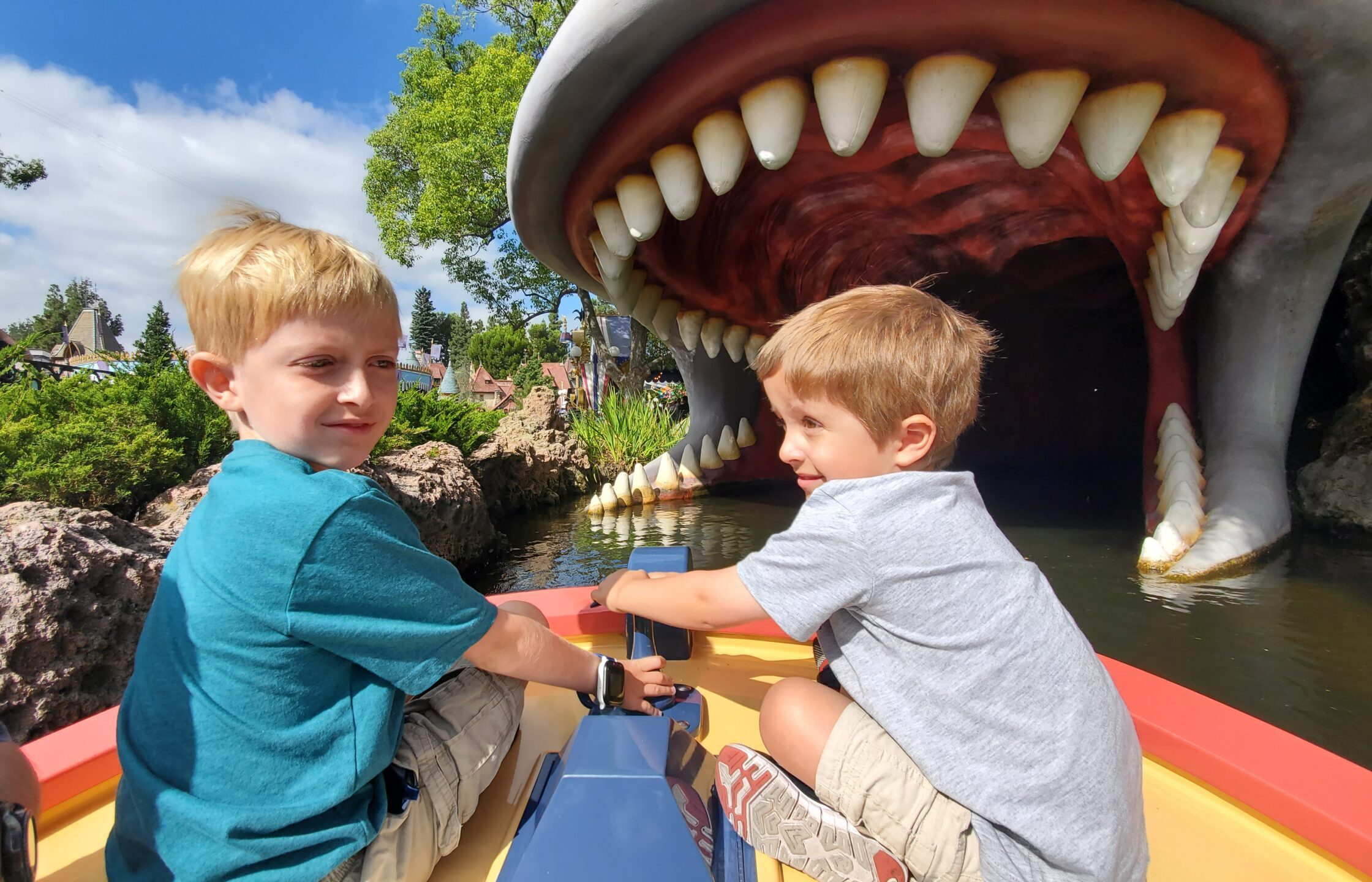 Two young children riding on the front of a Storybook Canal Boat about to enter the whale's mouth.
