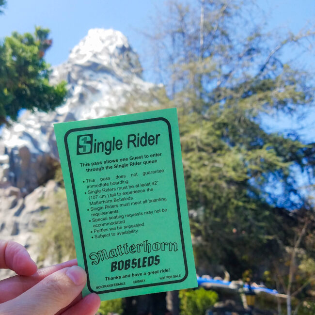 Single Rider voucher being held up with Matterhorn ride in the background
