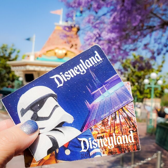 holding two Disneyland tickets , spread out, with Star Wars storm trooper on it, Disneyland ticket booth in background, purple blooms on tree
