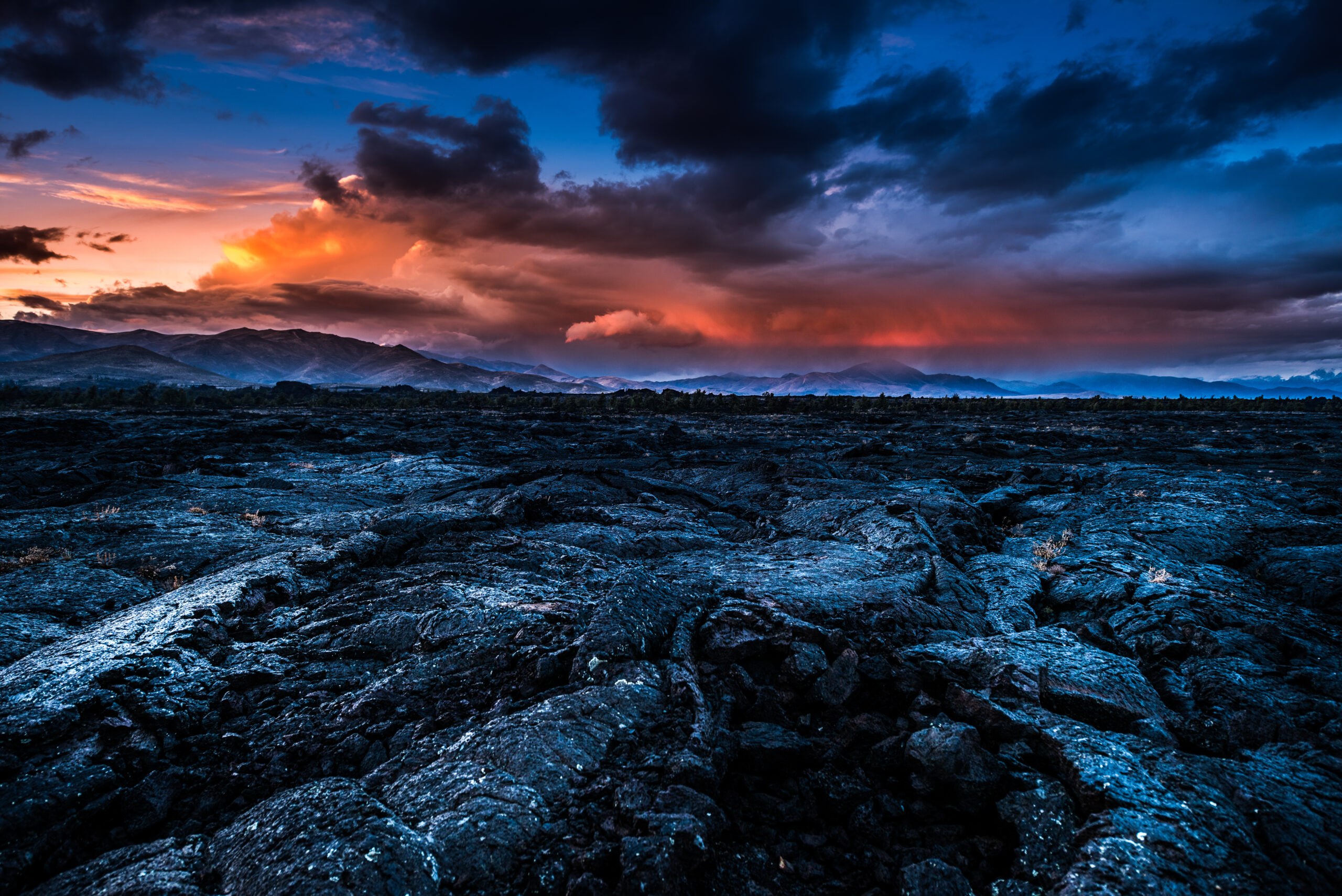 Craters of the Moon in Idaho, as the sunsets, with clouds in the sky.