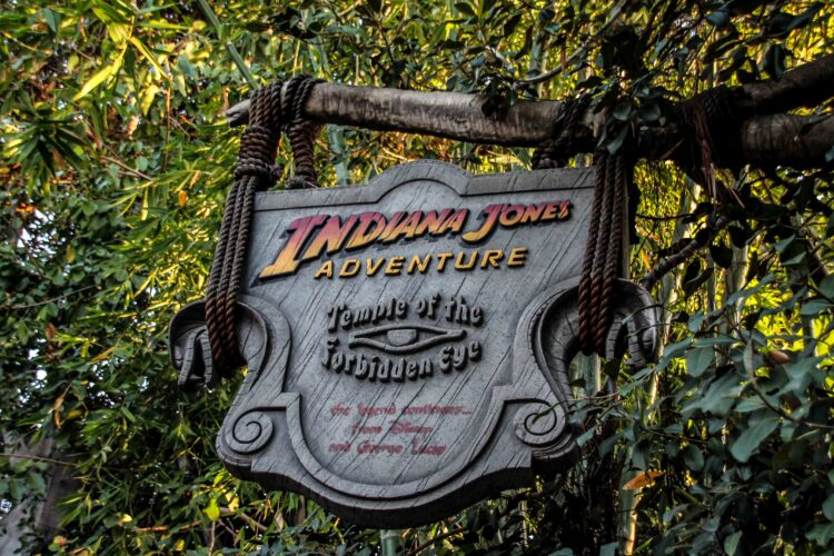 Sign for Indiana Jones adventure in Adventureland at Disneyland. This ride will be open when Disneyland Reopens. Sign has a forbidden eye image on it and looks to be made of stone, hung by rope from a branch
