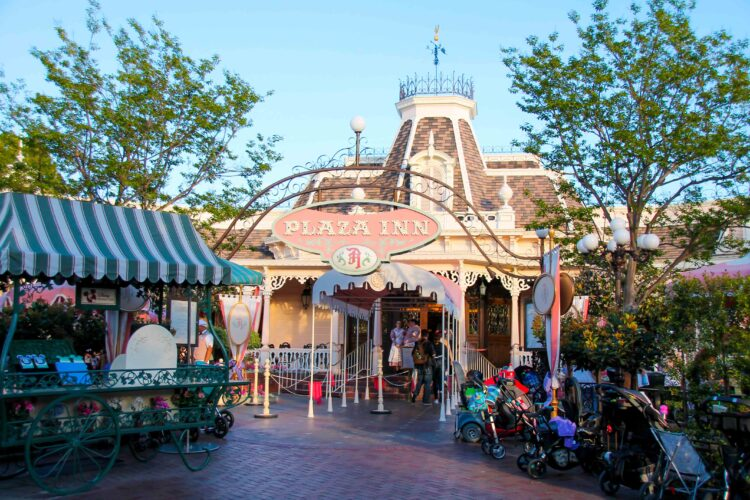 Plaza Inn at Disneyland with strollers parked outside, around sunset