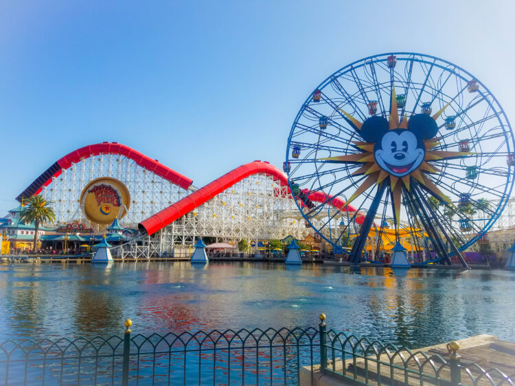 Pixar Pier at Disneyland from across the lagoon. Mickey's Funwheel and Incredicoaster in view. A train in the Incredicoaster is upside down on the loop