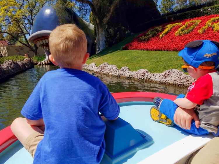 Young children sitting on front of boat, heading towards a giant whale on Disneyland's Storybook Canal Boat ride