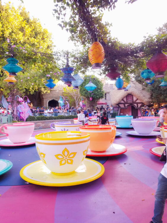 Tea Cups at Disneyland with guests leaving the ride. Paper lanterns above. This ride will be available when Disneyland Reopens