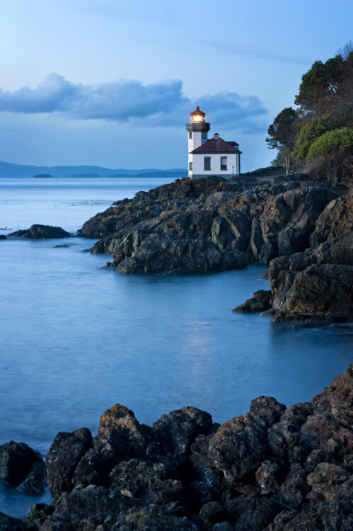 Lime Kiln Lighthouse at dusk, taken from nearby rocks jutting out into the ocean.