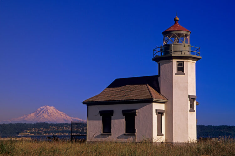 Point Robinson Lighthouse taken from the water side, showing land and Mt Ranier behind in the background.
